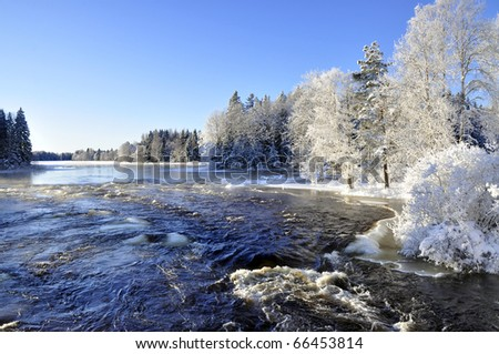 A river in winter surrounded by snow and trees - stock photo