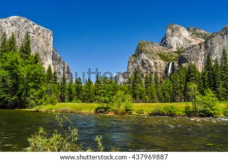 A river runs through the green Yosemite Valley between El Capitan and the mountains of the Sierra Nevada in California.