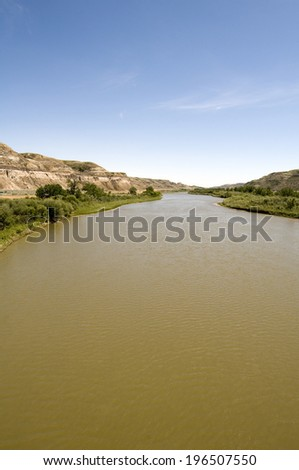 A river winding through lush green vegetation with hills on either side. - stock photo