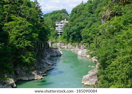 A river winding through the forest with rocky shores. - stock photo