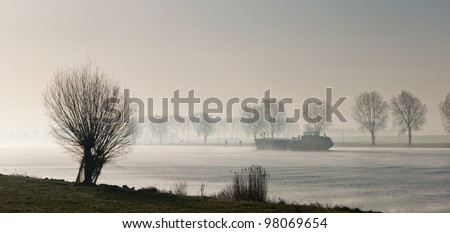 A river with trees on the banks in early morning mist. A foggy landscape in the Netherlands. - stock photo