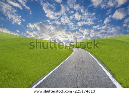 A road among green hills with a blue sky in background