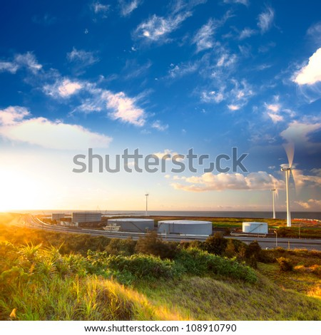 A road and windmills during sunset, made with a wide angle lens - stock photo