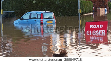 A Road Closed sign nearly underwater with a flooded car nearby.  - stock photo
