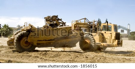A road crew uses a scraper. - stock photo