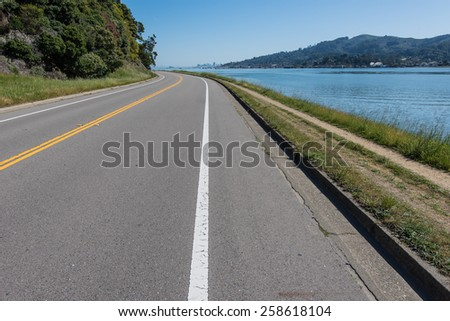 A road curves around a bend next to water with San Francisco in the background - stock photo