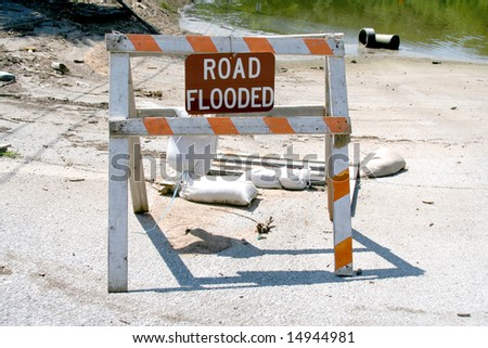 "A ""Road Flooded"" Sign in front of flood waters that have hammered the midwestern U.S."