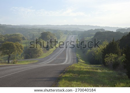 A road in the Texas Hill Country near sundown during spring - stock photo