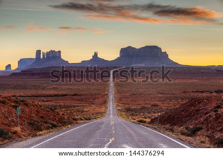 A road leading to Monument Valley at sunset. - stock photo