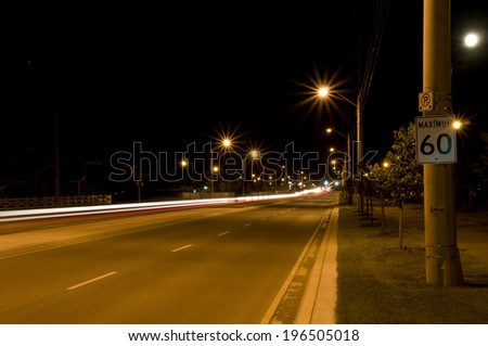 A road lighted by streetlights at night with a speed limit sign. - stock photo