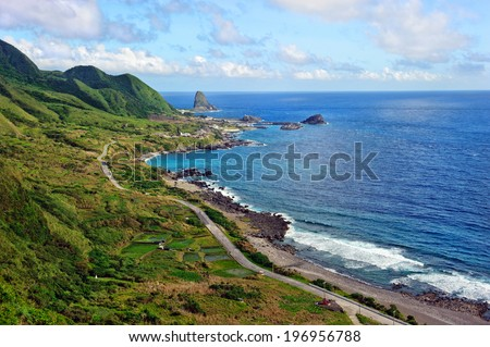 A road running along a coast with lush green hills on the other side. - stock photo