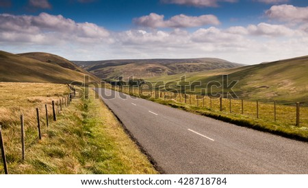 A road runs through sheep pastures in the Moorfoot Hills in Scotland's Southern Uplands.