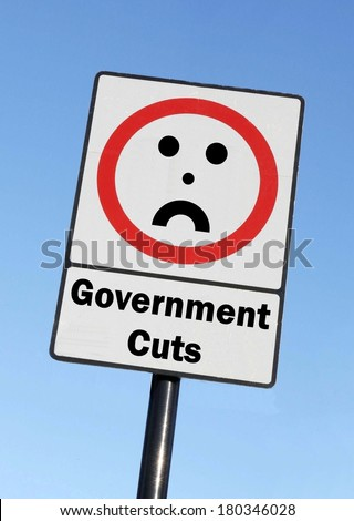 A road traffic sign with a Government Cuts concept with a clear blue sky background.  - stock photo