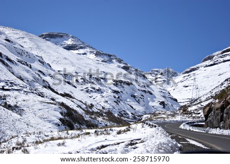 A road winds up a pass in the snow covered Maluti mountains in rural Lesotho, Africa. - stock photo