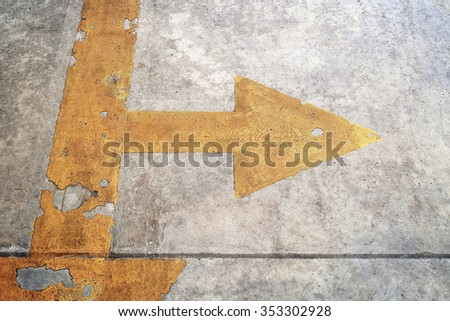 A road with yellow arrow two way on concrete background - stock photo