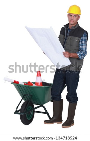A road worker checking plans. - stock photo