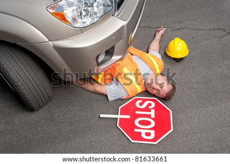 A road worker is hit by a car. - stock photo