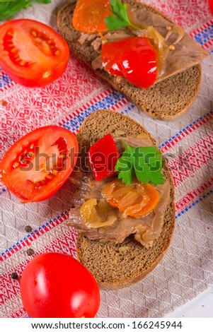 A roast beef sandwich on grain bread with pepper, carrots, onions and tomatoes