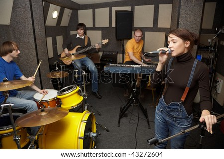 a rock band working in studio. vocalist girl is singing. focus on clothes of vocalist girl - stock photo
