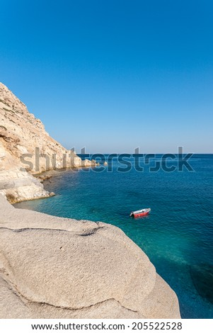 A rock by the turquoise waters of a calm, crystal clear sea, located in the island of Ikaria, Greece, during daylight in the summer.