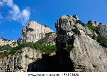 A rock cliff against a blue sky in the early morning at Fangdong Scenic Area on Yandangshan mountains located in Zhejiang province China.