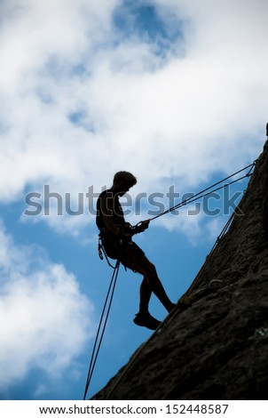 A rock climber ascends to the top