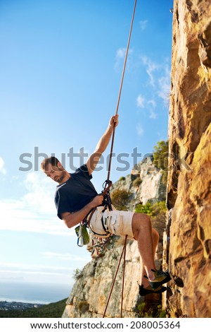 A rock climber going down a steep mountain with a rope against a blue sky - stock photo
