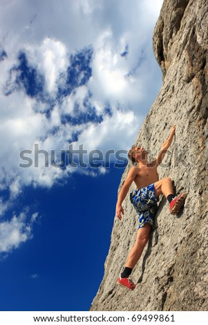 A rock climber on a rock against the blue sky