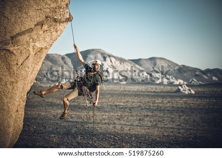 A rock climber rappelling past an overhang in Joshua Tree National Park, California, on a summer evening.