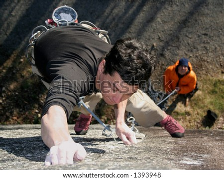 A rock climber struggles to hold on. - stock photo
