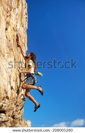 A rock climbing man reaching for a grip on a steep mountain in the outdoors - stock photo