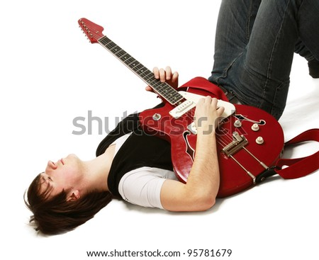 A rock guitarist lying on the floor, isolated on white background - stock photo
