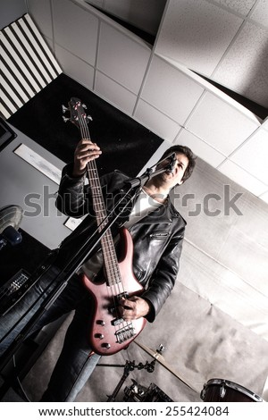 A Rock singer playing bass in the rehearsal Studio.