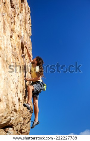A rockclimbing man reaching for a grip on a steep mountain in the outdoors - stock photo