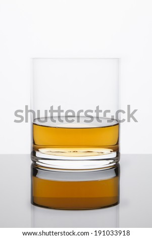 A rocks glass with Whiskey sits atop a reflective surface on a bright white background