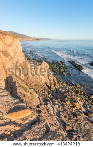 A rocky cliff view of the Pacific ocean at low tide in Carpinteria, California. - stock photo