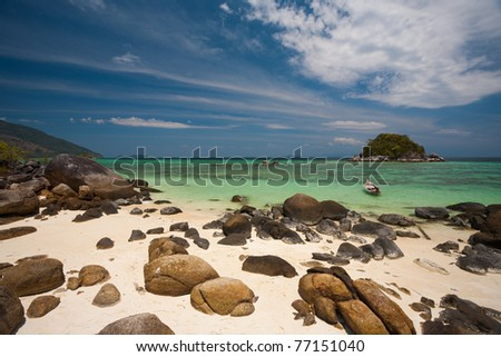 A rocky sand beach and beautiful coral is seen through the crystal clear water of island paradise, Koh Lipe in Thailand. Horizontal copy space