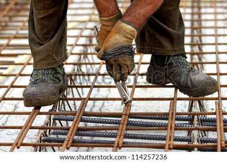 a rodbuster or iron worker working on a reinforcing rebar