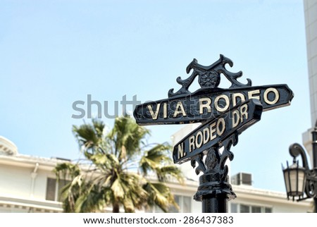 A Rodeo Drive sign in Beverly Hills on a sunny day.