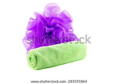 A roll of green towel with purple sponge on a white background - stock photo
