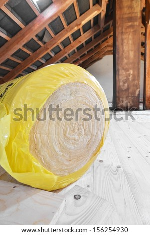 A roll of insulating glass wool on an attic floor - stock photo