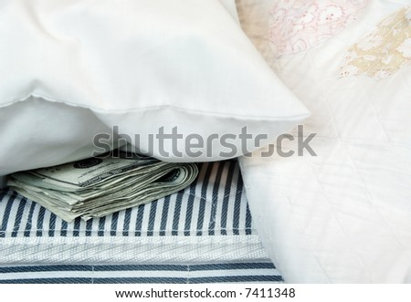 A roll of money tucked in a mattress for safekeeping. - stock photo