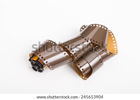 A roll of old 35mm photographic film on a white background - stock photo