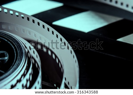 A roll of photographic film. Movie clapper for shooting Films - stock photo