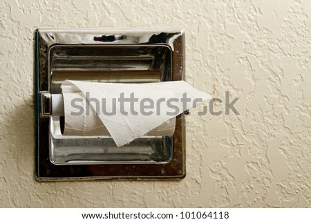 A roll of toilet paper on a dirty holder that is almost empty - stock photo