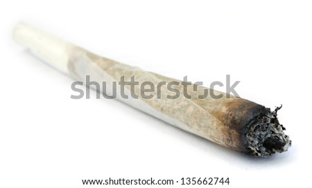A rolled marijuana joint half burnt, isolated on white. - stock photo
