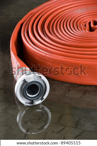 A rolled up firehose on the floor in a fire station used by firefighters - stock photo