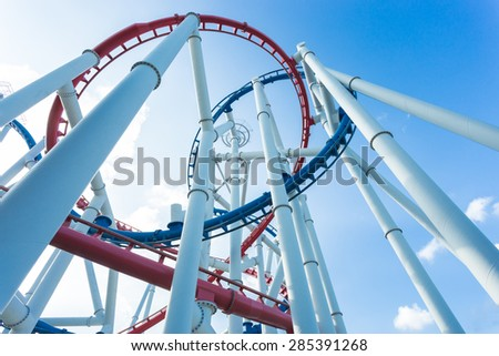 a roller coaster's loop with blue sky - stock photo