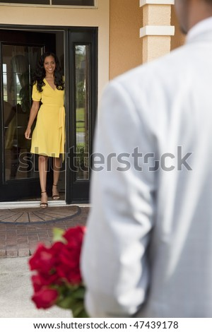 A romantic African American man bringing flowers to his happy wife or girlfriend who is standing waiting for him at the door of their home. - stock photo