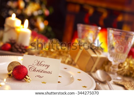 A romantic Christmas dinner table setting with candles and Christmas decorations. On the plate a note with the words 'Merry Christmas' is waiting for a guest. - stock photo